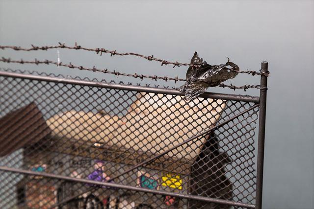 ゴミがフェンスに引っ掛るゴミ箱のミニチュア